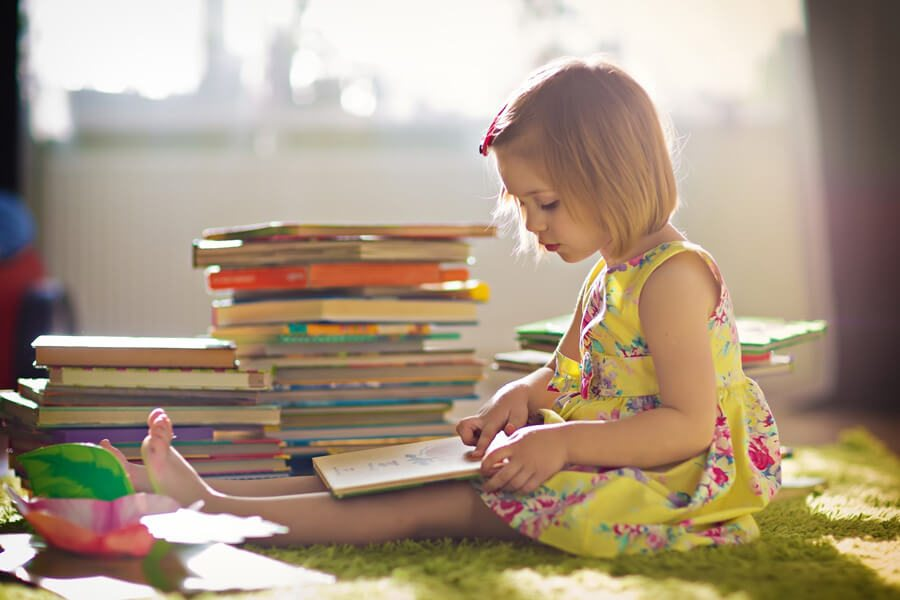 Young girl reading a stack of books