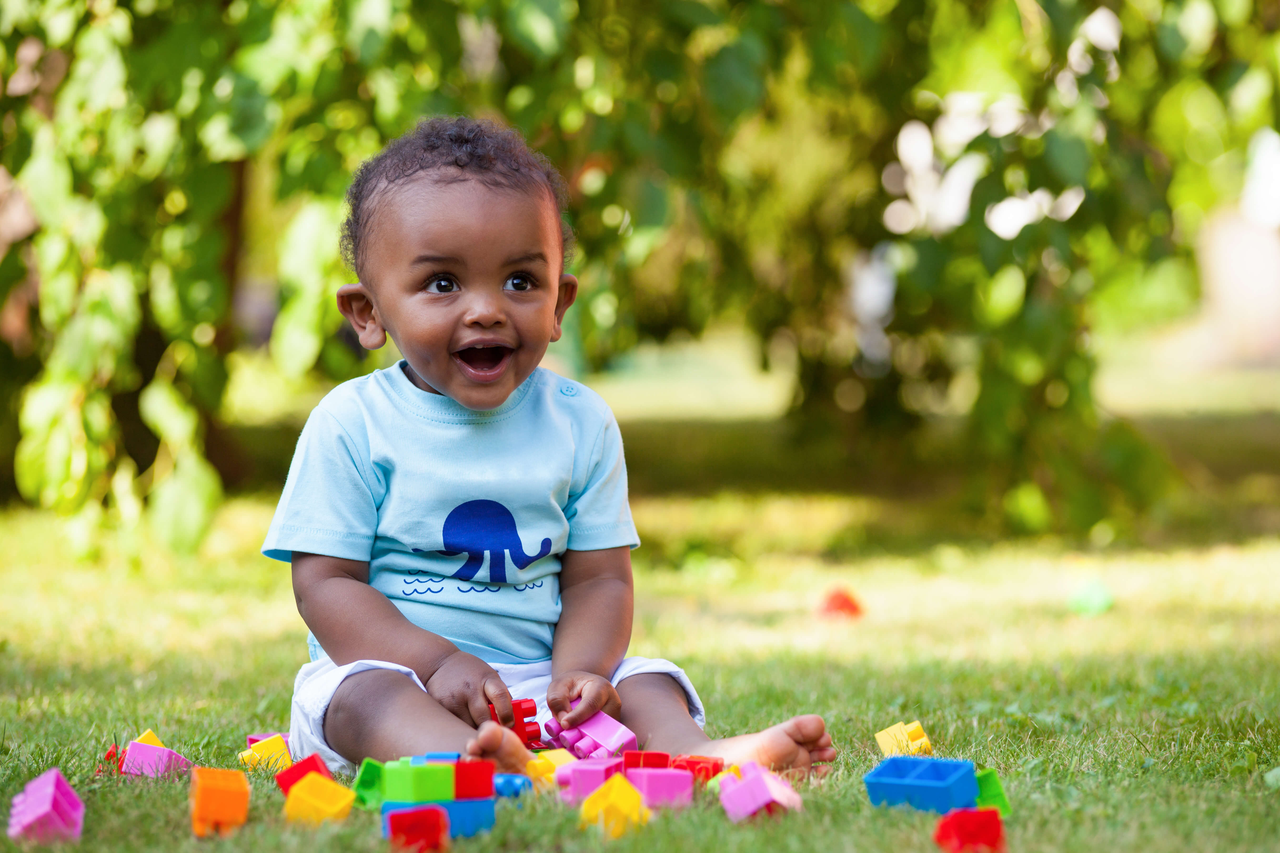 Baby playing with blocks in the grass