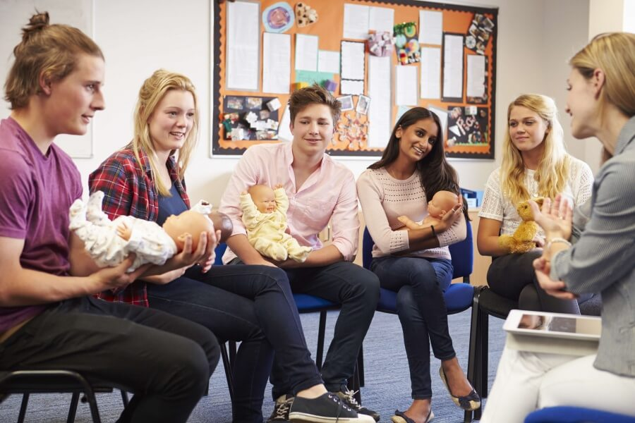 Group of adults sitting in a circle holding baby dolls