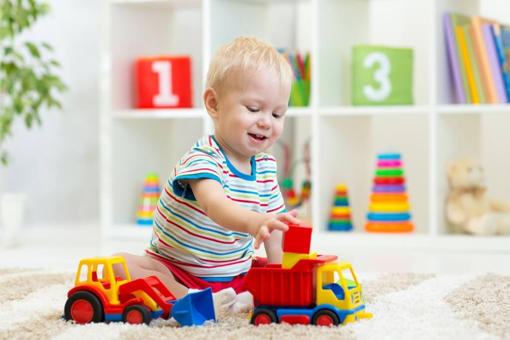 Child playing with blocks and toy trucks