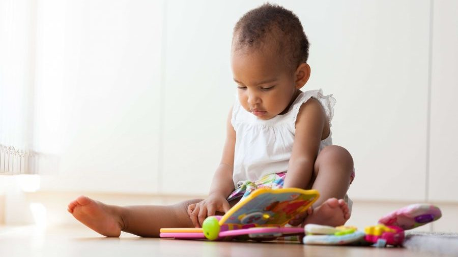 Baby reading a book on the floor