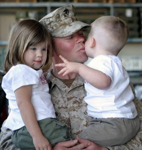 man in military uniform holding two children