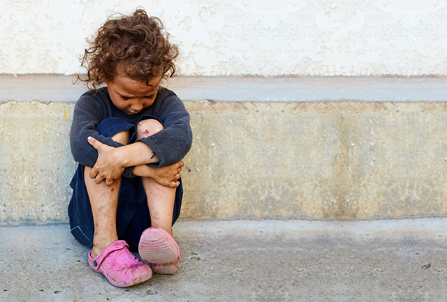 young homeless girl sits alone outside