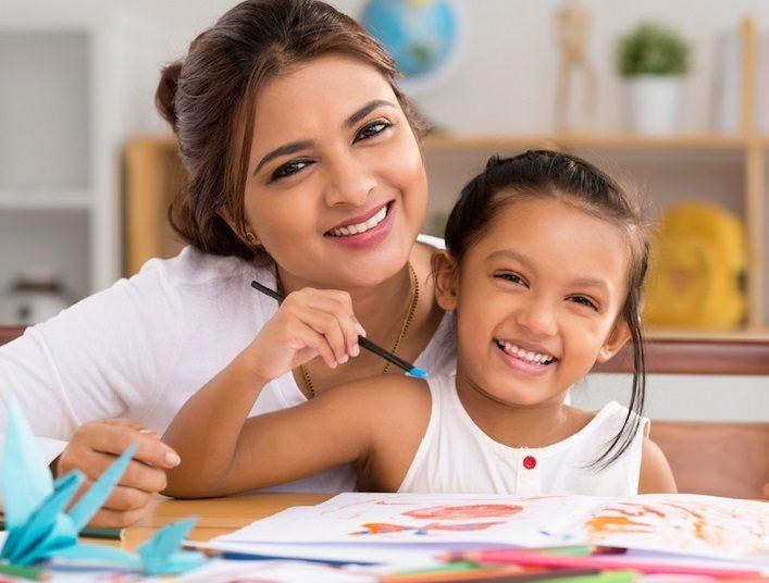 Maestra y niña pintando