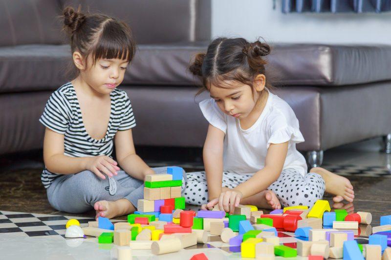 Dos niñas pequeñas juegan con bloques en el suelo de una casa