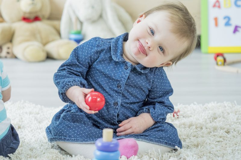 A baby girl is sitting on the carpet and making a funny face while playing with toys