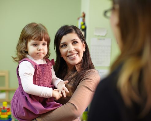 Mother holding her daughter and facing child care provider