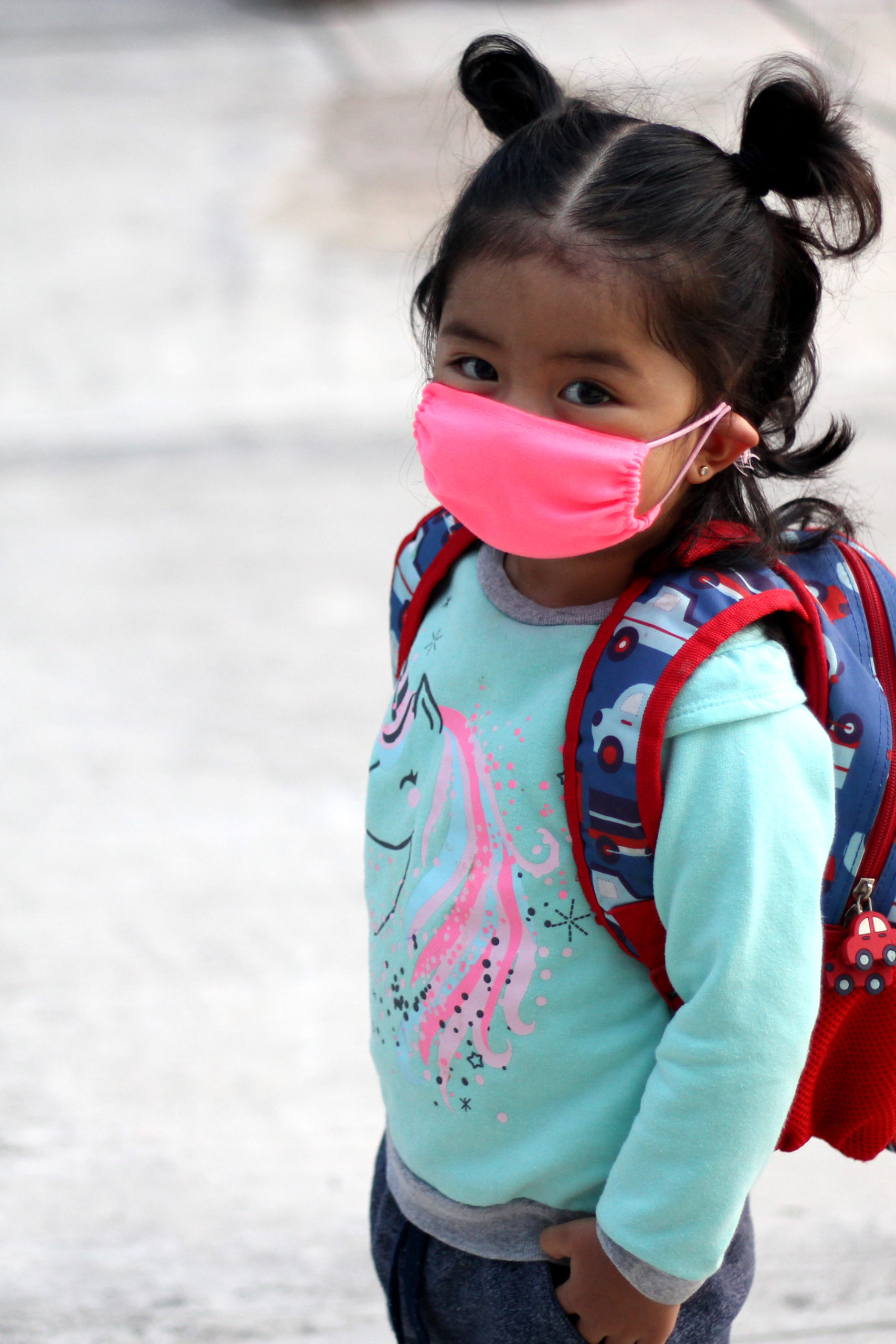 Young girl with mask and backpack