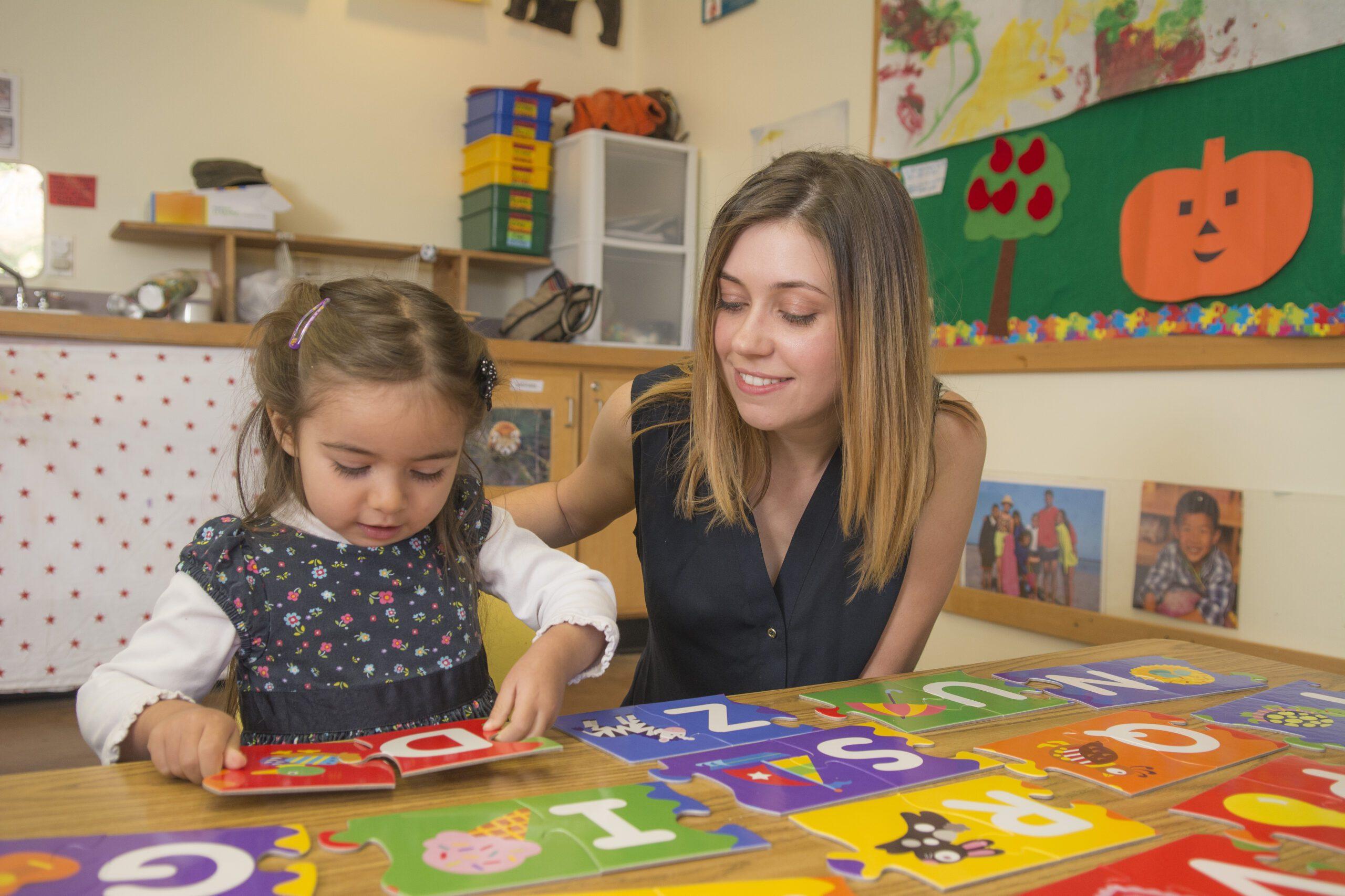 preschool teacher reads a book with a young girl