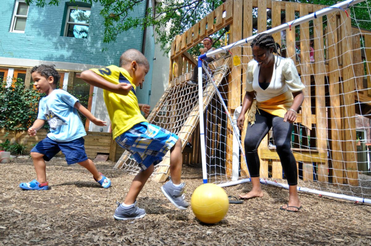 Boy plays soccer with his child care teacher