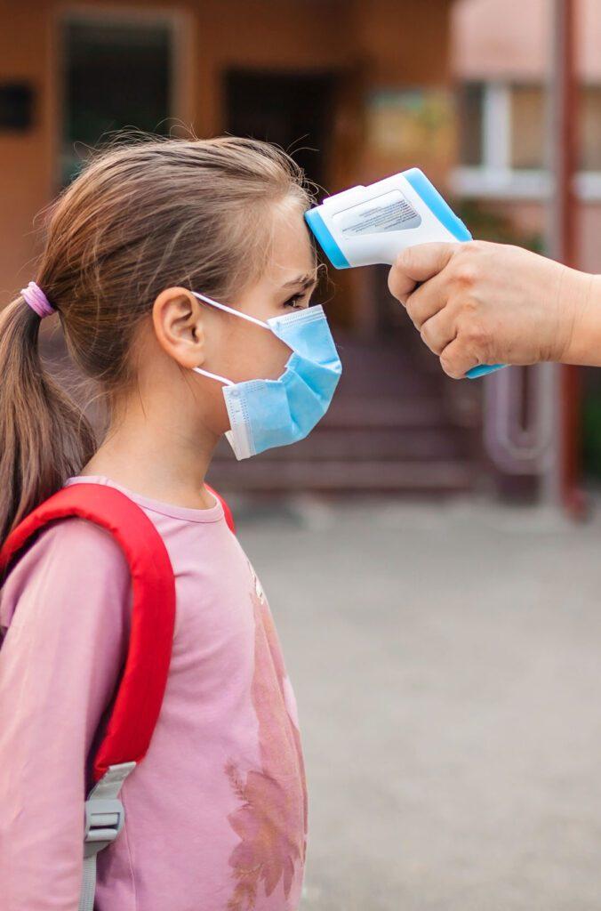 girl gets her temperature taken before entering school building